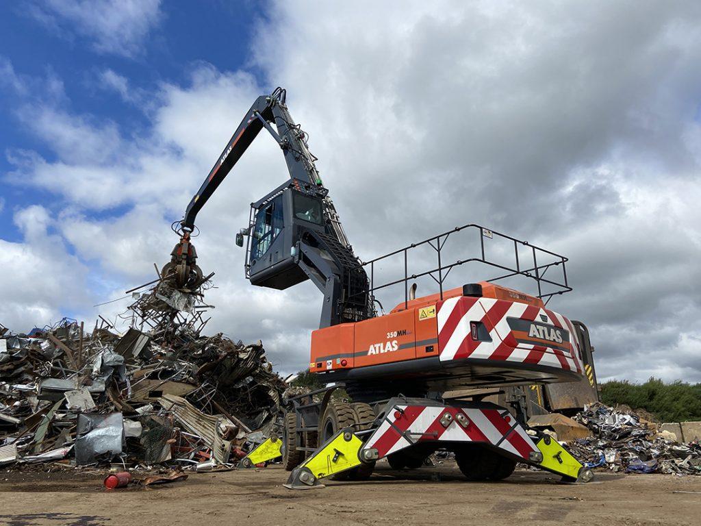 Atlas scrap handler moving scrap metal with grab