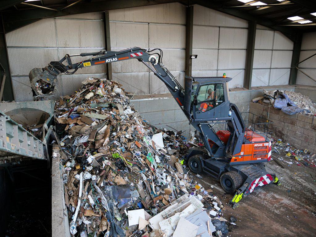 Atlas 200MH Material Handler loading waste onto conveyor